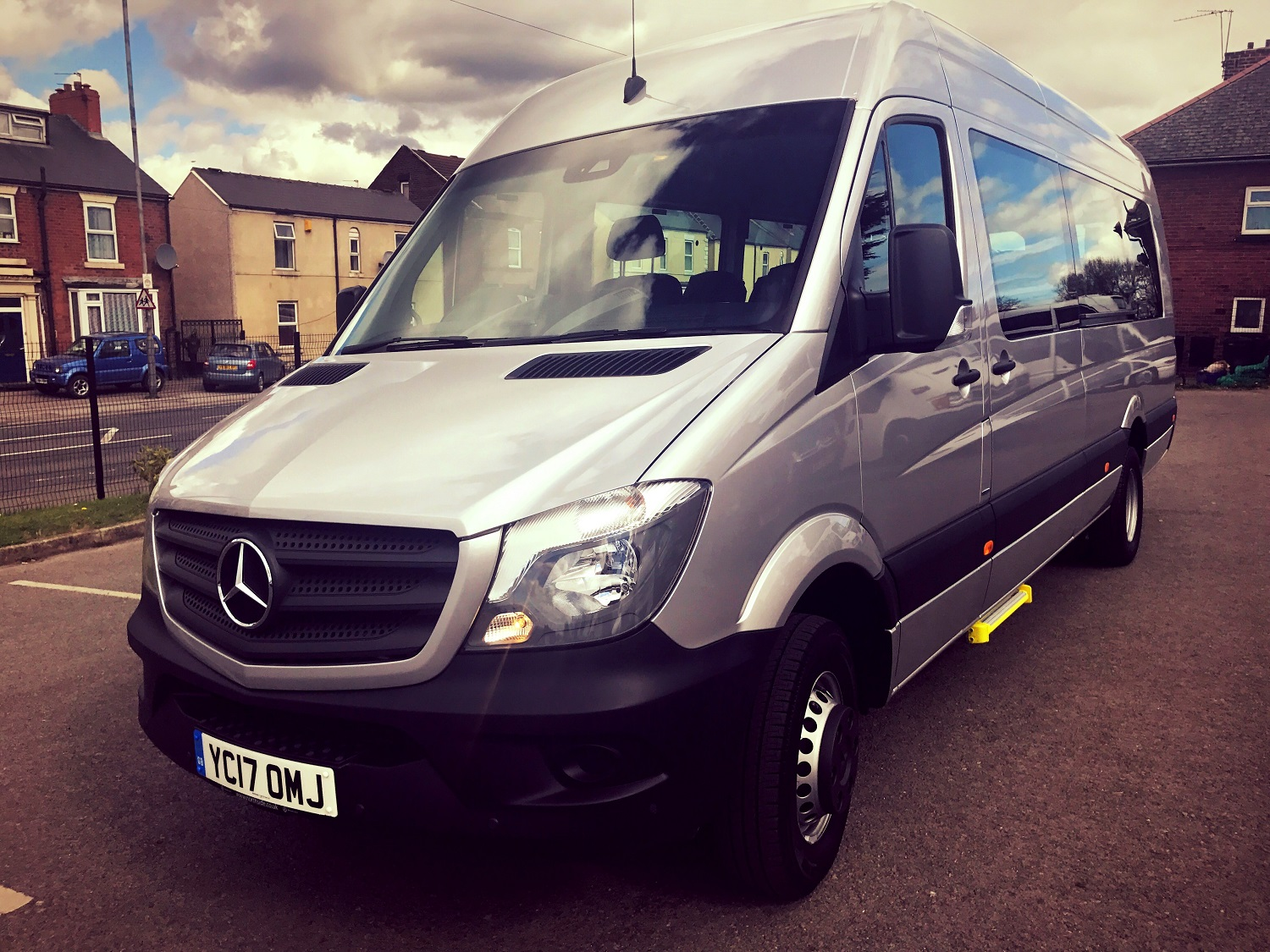 The outside of our silver 2017 Mercedes Sprinter 16 Seater Minibus. The front and left hand side of the minibus are shown.
